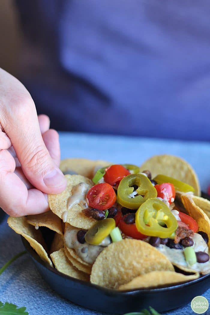 Hand scooping tortilla chip into vegan nachos.