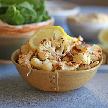 Easy roasted cauliflower cooked in air fryer in bowl.