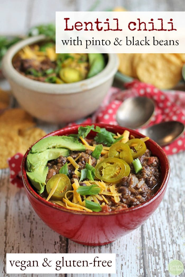 Text: Lentil chili with pinto and black beans. Vegan & gluten-free. Bowls of lentil chili, red napkin, and spoons.