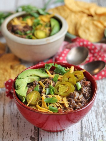 Lentil chili with pinto and black beans in red bowl with avocado slices, jalapeno peppers, and onions.