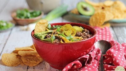 Red bowl of spicy lentil chili with beans. Topped with jalapeno peppers, avocado, and non-dairy cheese.