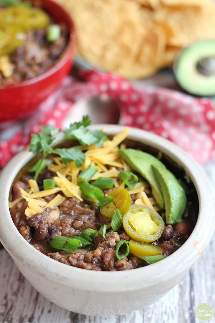 Lentil chili with pinto and black beans in bowl with non-dairy cheese, cilantro, and avocado.