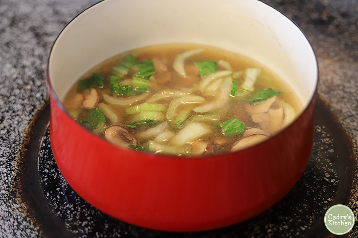 Red pot on stove with bok choy, mushrooms, and miso broth.