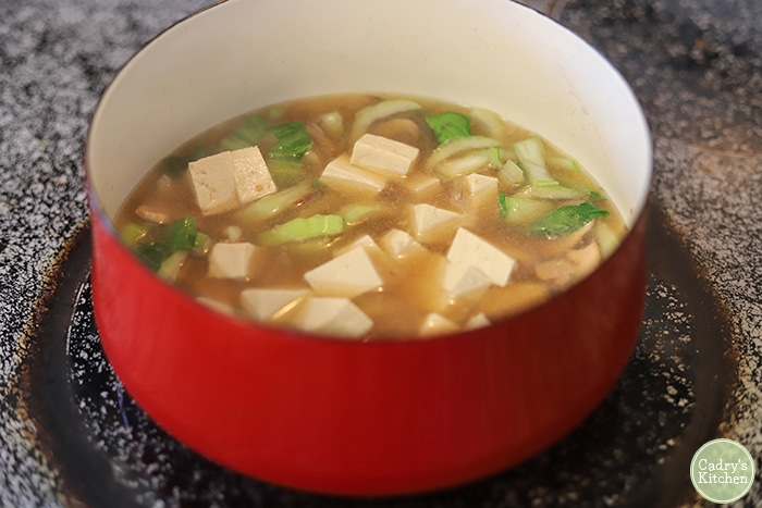 Pot with cubed tofu, bok choy, and mushrooms.