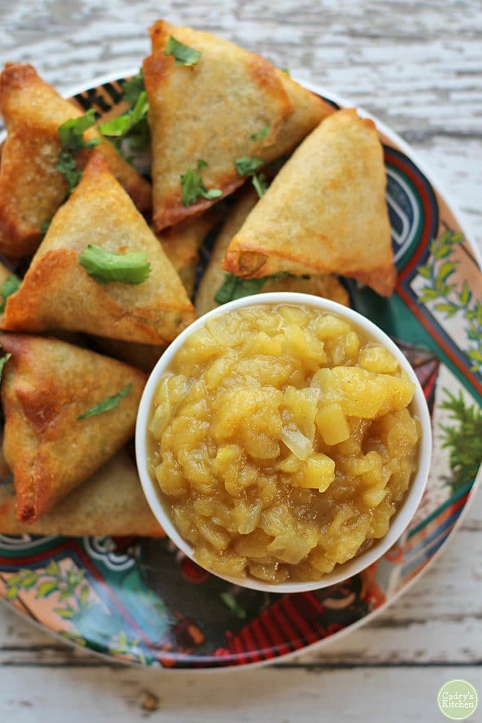Overhead apple chutney in bowl. Trader Joe's vegetable samosas on plate.