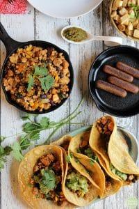 Overhead breakfast tacos on plate, Field Roast breakfast sausage in pan, and tofu scramble in skillet.