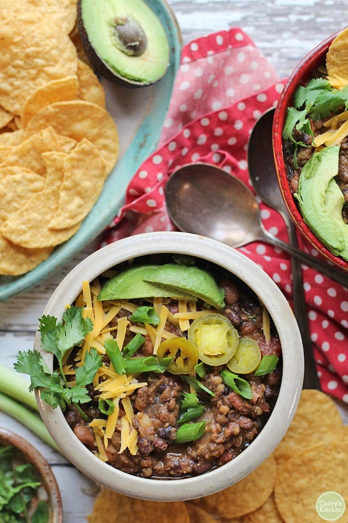 Overhead lentil chili in beige bowl with non-dairy cheese, avocado, and onions.