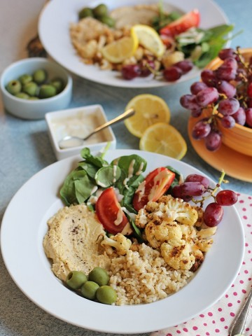 Brown rice bowl with hummus, olives, roasted cauliflower, and spinach salad.