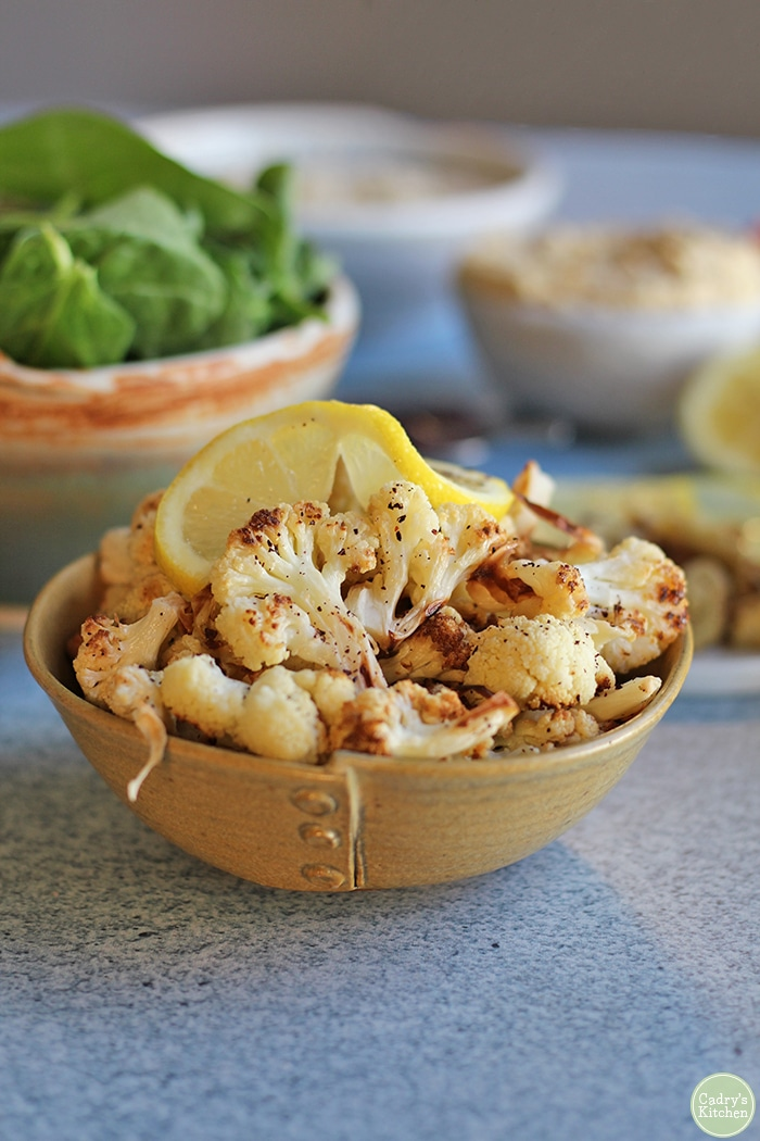 Close up easy roasted cauliflower in small bowl with lemon slice.