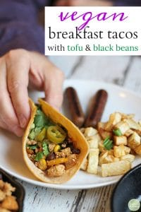 Text: Vegan breakfast tacos with tofu & black beans. Hand holding breakfast taco on plate with potatoes and veggie sausage.