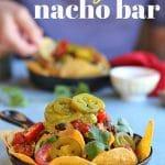 Text: Vegan nacho bar. Hand scooping into nachos in background. In foreground, cast iron skillet filled with vegan nachos.