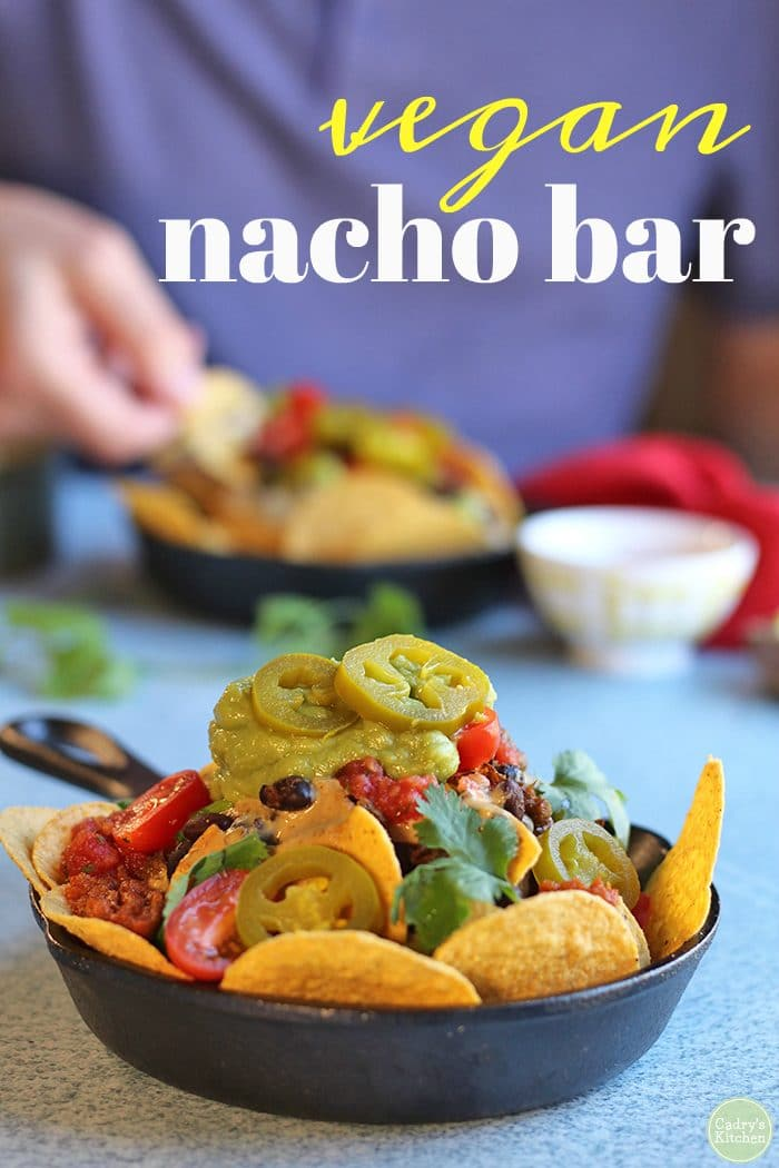 Text: Vegan nacho bar. Hand scooping into nachos in background. In foreground, cast iron skillet filled with vegan nachos.