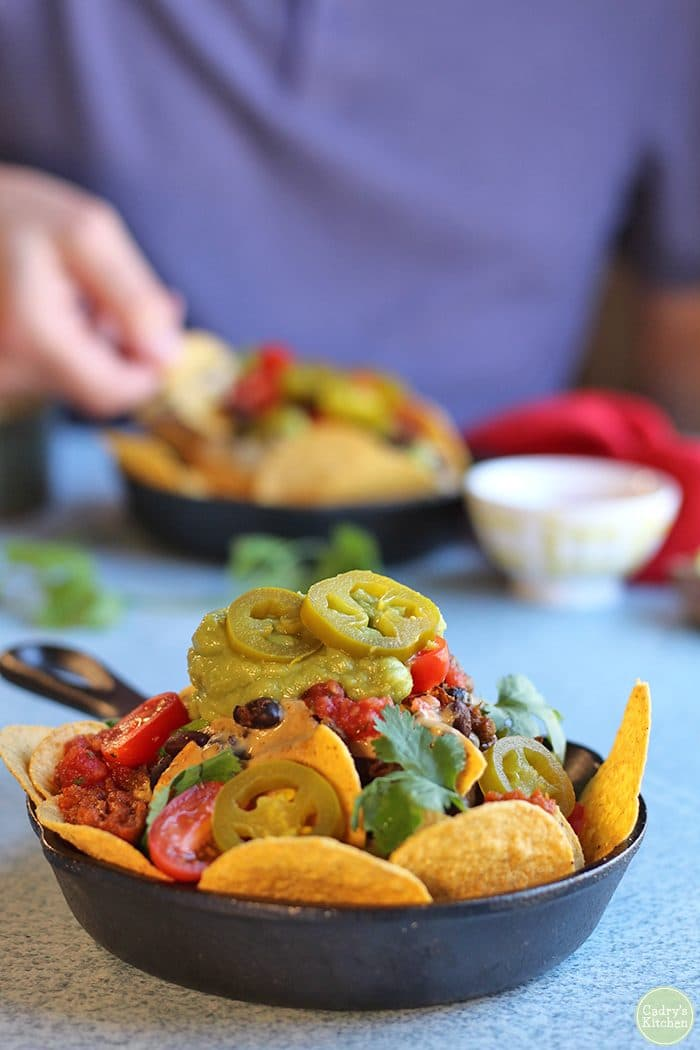 Vegan nacho bar with nachos in a cast iron skillet.