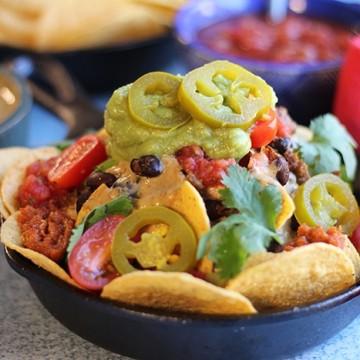 Close up vegan nachos in mini cast iron skillet with salsa, guacamole, and vegan chili cheese dip.