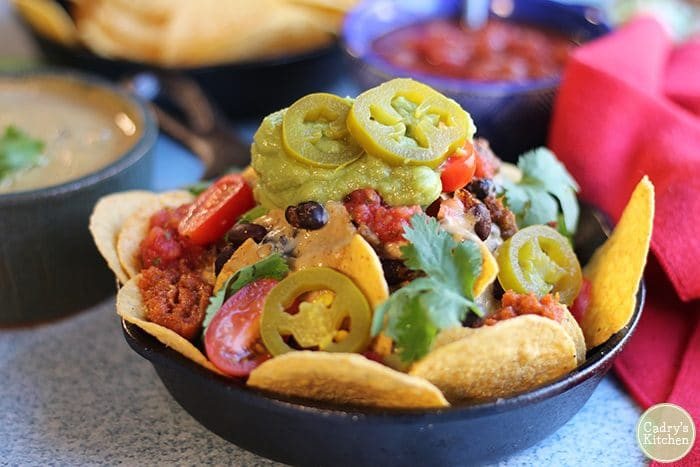 Close up vegan nachos in mini cast iron skillet with salsa, guacamole, and vegan chili cheese dip.