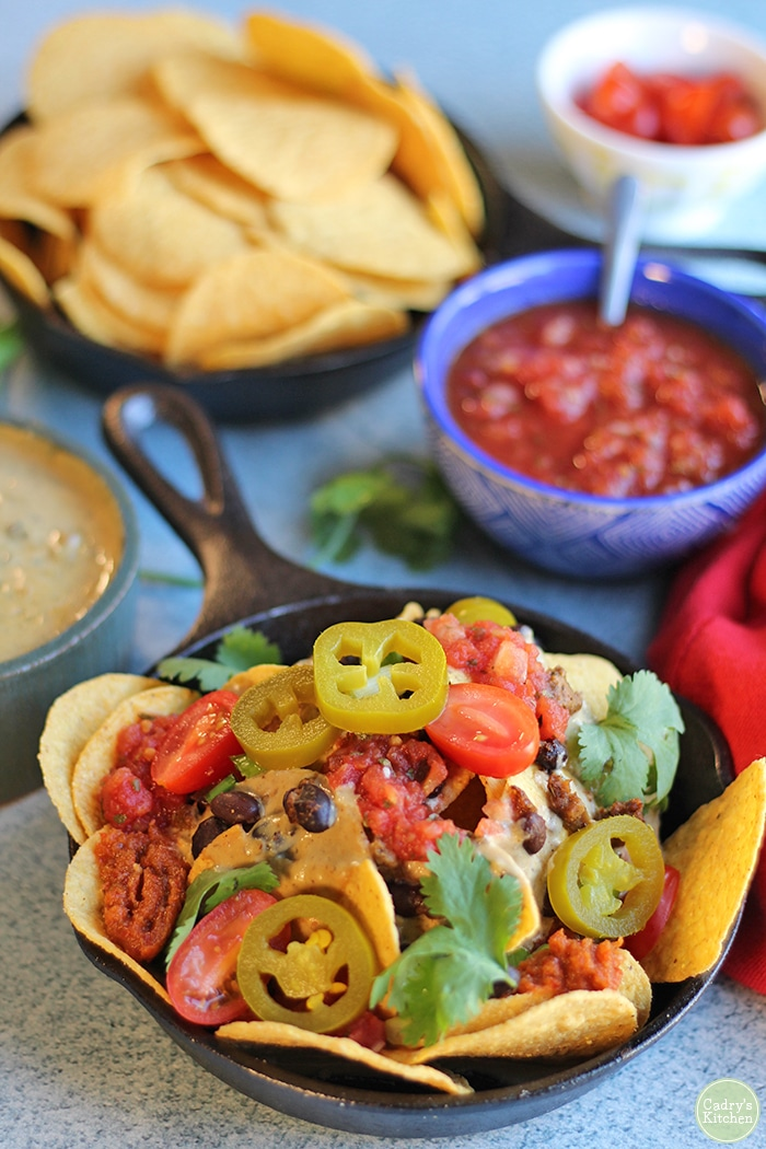 Vegan nacho bar with salsa, chips, and nachos in a cast iron skillet. Nacho cheese dip made with nutritional yeast.