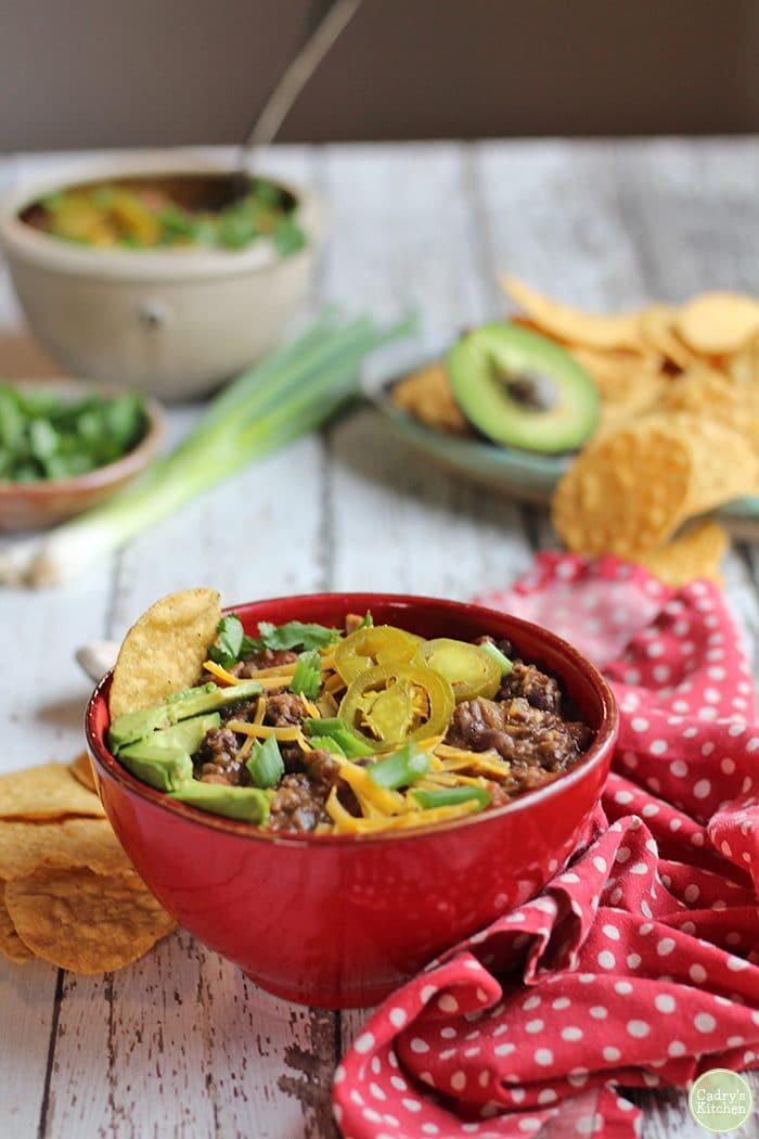 Lentil chili in red bowl with avocados, non-dairy cheese, onions, and jalapeno pepper slices.