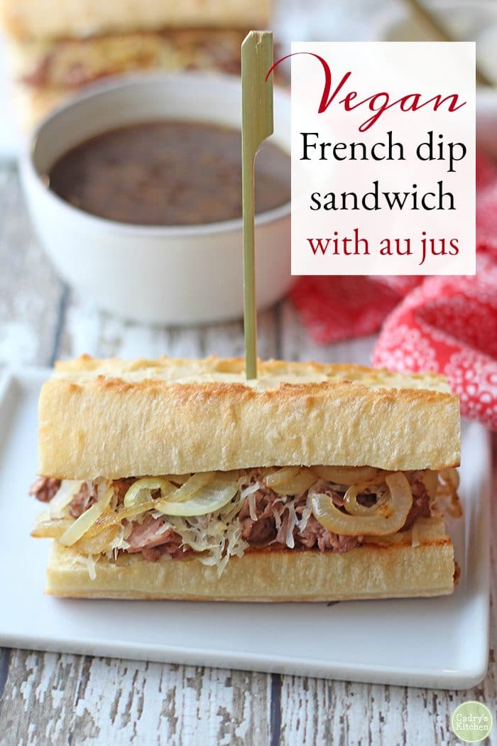 Text: Vegan French dip sandwich with au jus. Vegan French dip sandwich with sauteed onions and non-dairy cheese on plate. Vegan au jus in background.
