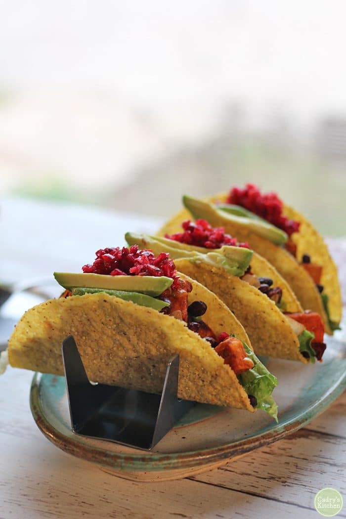 Sweet potato black bean tacos with cranberry salsa on platter.