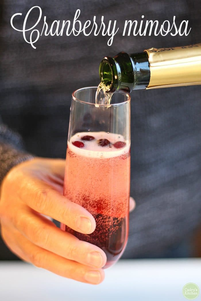 Text: Cranberry mimosa. Sparkling wine being poured into glass with cranberries and cranberry juice.