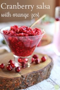 Text: Cranberry salsa with orange zest. Cranberry salsa in martini glass on wood board.