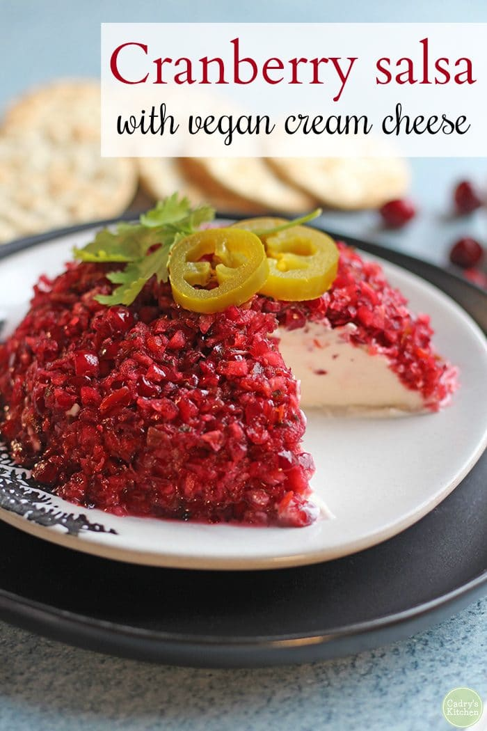 Text: Cranberry salsa with vegan cream cheese. Cranberry salsa with cream cheese on plate. Crackers in background.