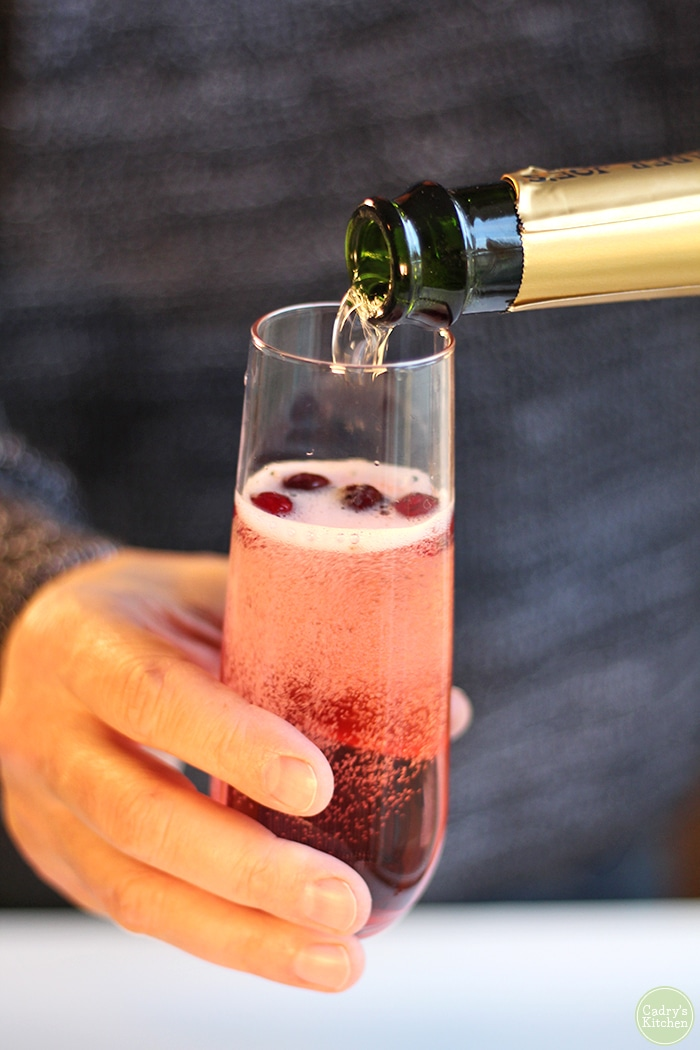 Hand pouring sparkling wine into glass with cranberries and cranberry juice.