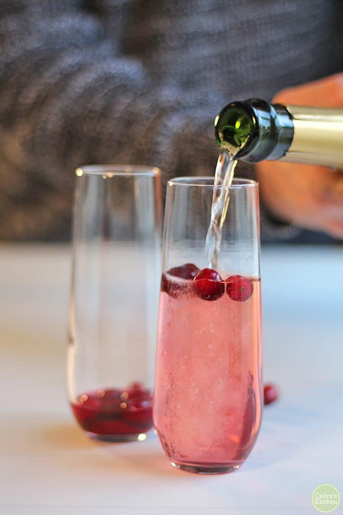 Sparkling wine being poured into champagne flute with cranberries and cranberry juice.