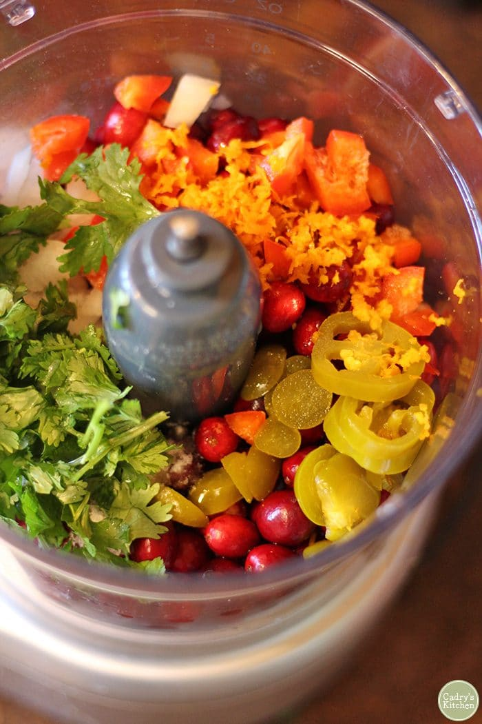 Ingredients for cranberry salsa in food processor.