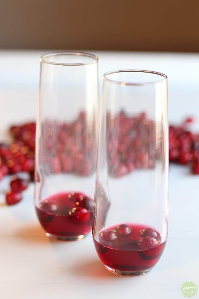 Champagne flutes with cranberries and cranberry juice.