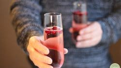Hands holding cranberry mimosas in champagne glasses.