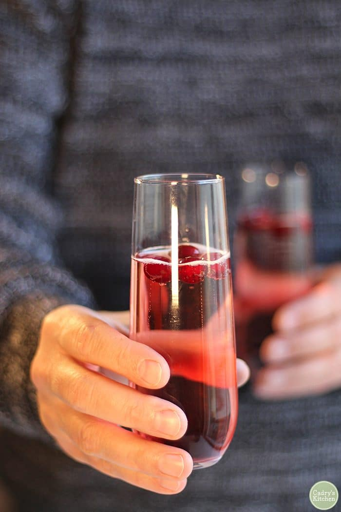 Hand holding cranberry mimosas in champagne flutes.