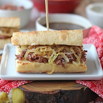 Vegan French dip sandwich on plate with red napkin.