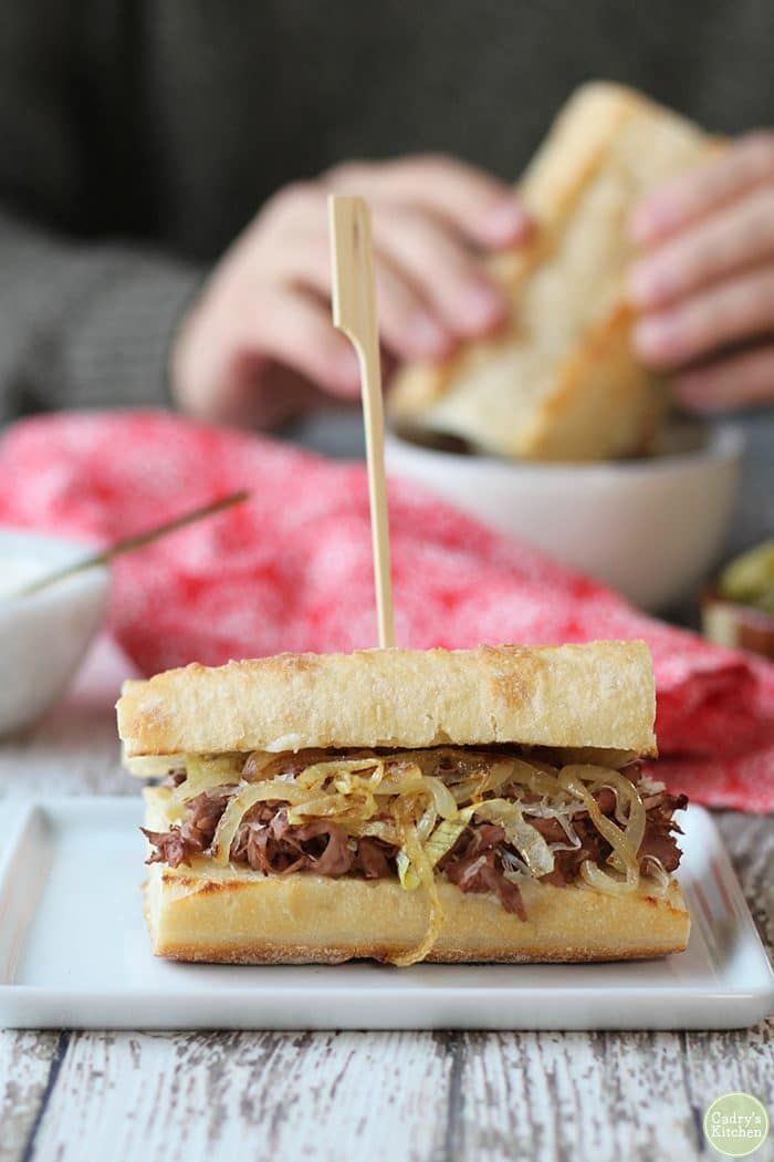 Vegan French dip sandwich on table with red napkin.
