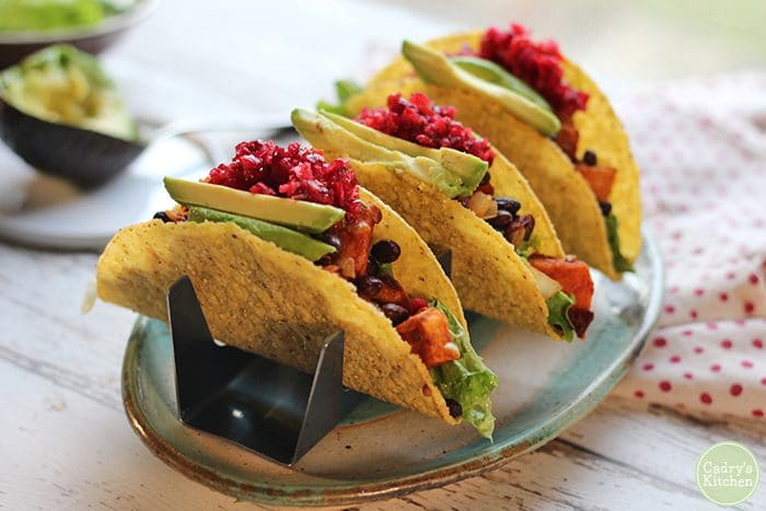 Tacos with hard corn shells, topped with avocado and cranberry salsa in taco holders.
