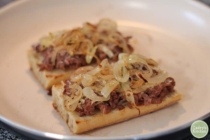 Open face vegan French dip sandwiches in skillet.