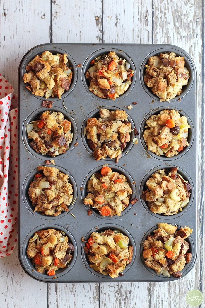 Overhead stuffing muffins in muffin pan on white table.
