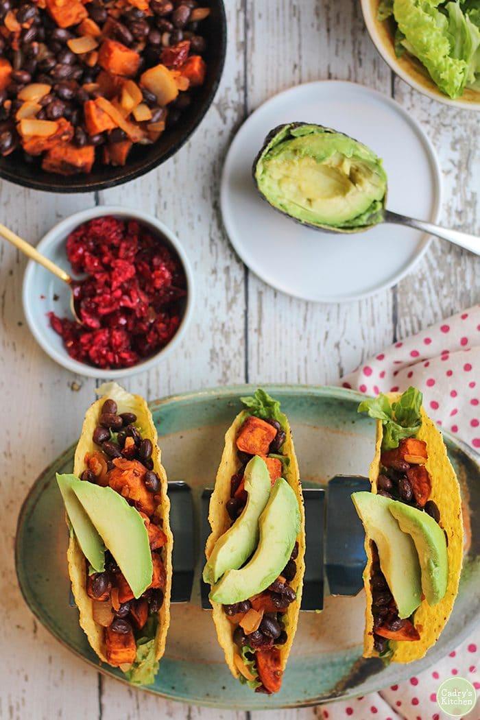 Overhead sweet potato black bean tacos, cranberry salsa, and avocado.