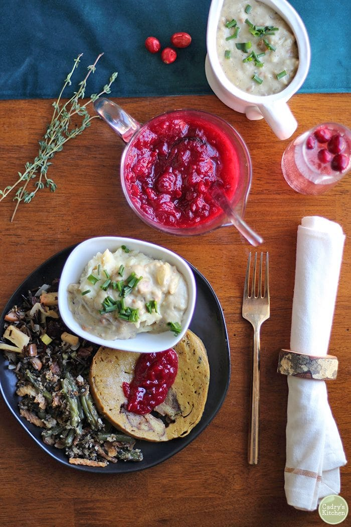 Overhead vegan Thanksgiving dinner with mashed potatoes, seitan, cranberry sauce, and cranberry champagne mimosa.