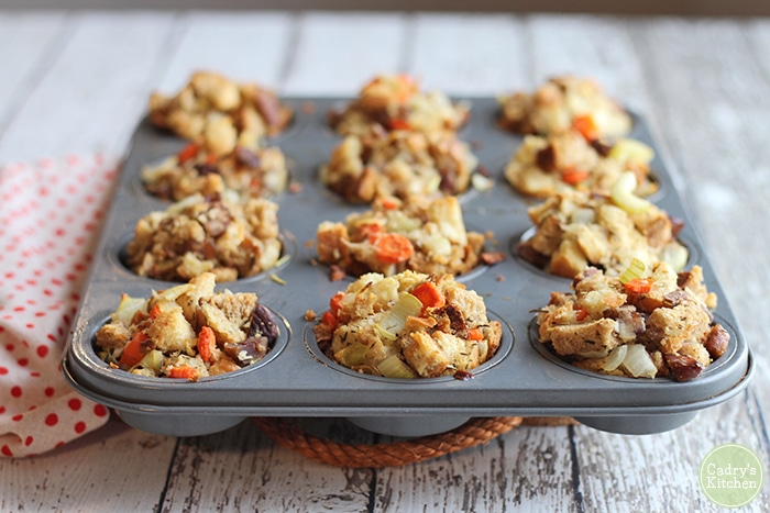 Stuffing muffins in muffin tin on table.