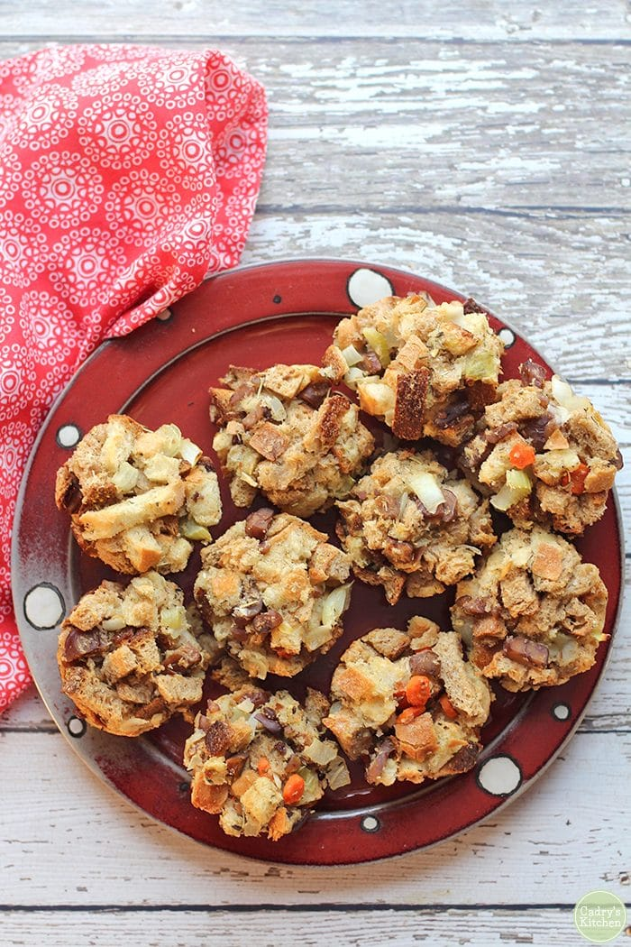 Overhead stuffing muffins on polkadot plate on white table with red napkin.