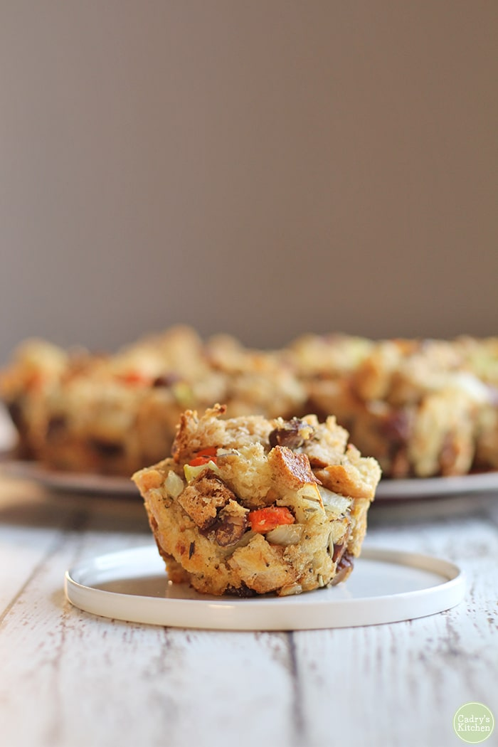 Stuffing muffin on small plate. Platter of stuffing muffins in background.