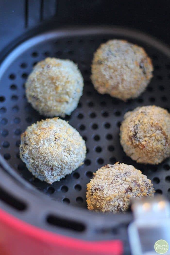 Vegan arancini in air fryer basket.