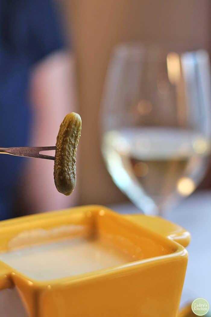Fondue fork spearing cornichon over fondue pot.