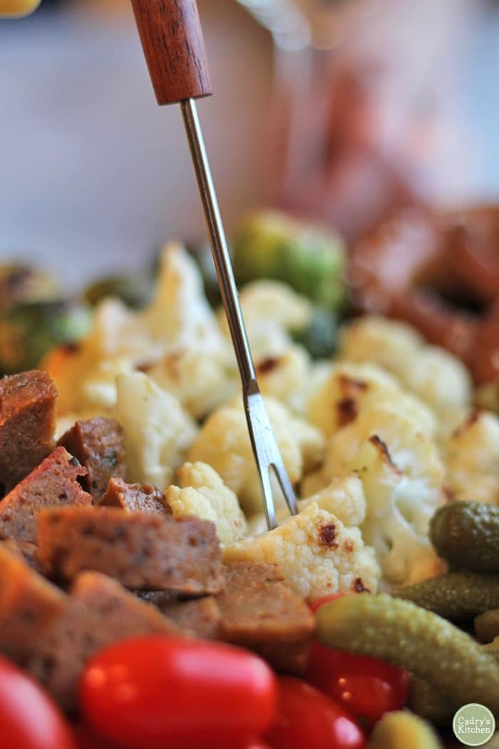 Fondue fork spearing roasted cauliflower.
