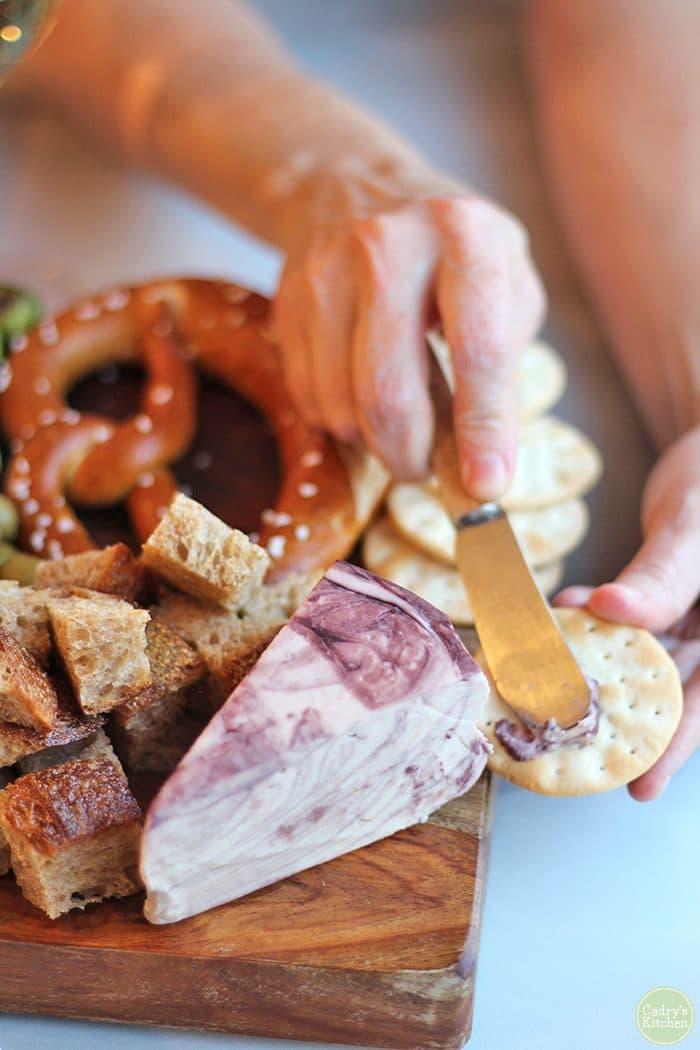 Hand smearing Havarti Reserva vegan cheese onto cracker.