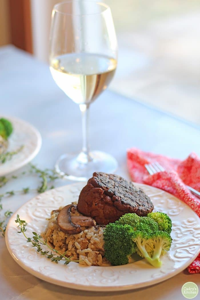 Vegan risotto on plate with seitan steak and steamed broccoli.