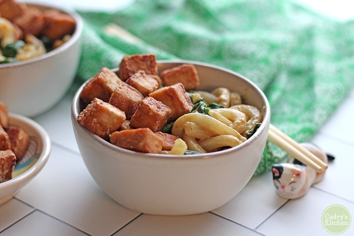 Peanut butter noodles & spinach in bowl with fried cubes of tofu.