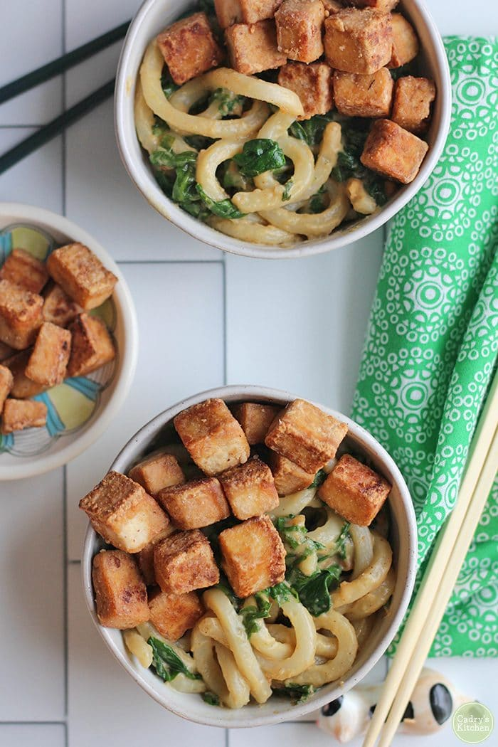 Overhead two bowls with peanut butter noodles, spinach, and fried tofu cubes.