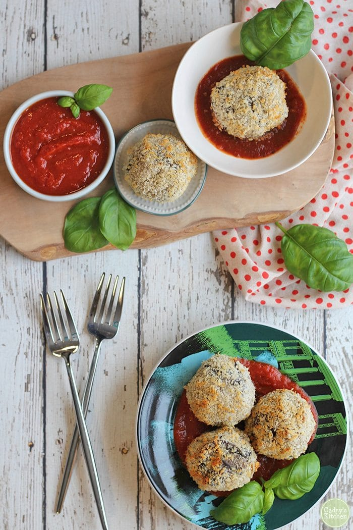 Overhead vegan arancini on plate, forks, and marinara.